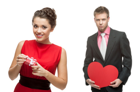 young smiling woman and handsome man holding red heart isolated on white background photo