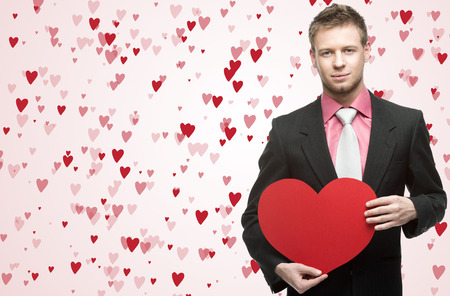 handsome men hold big red heart over small flying hearts on background photo
