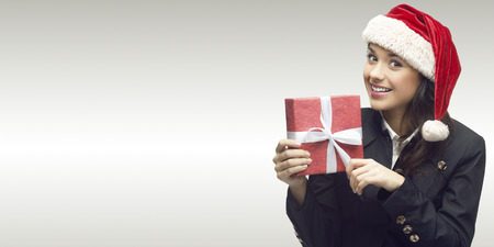 business woman in santa hat holding gift over gray background photo