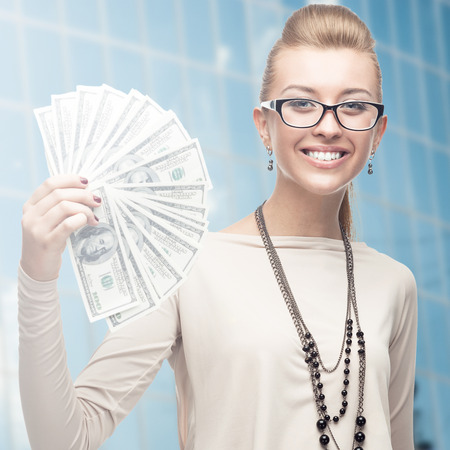 smiling young business woman standing over blue background photo