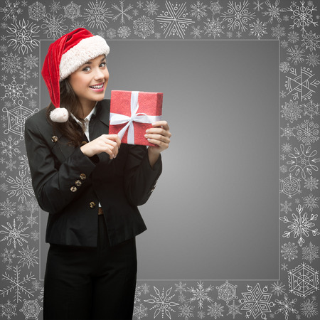 business woman in santa hat holding sign over gray snowflakes background photo