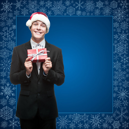 businessman in santa hat holding gift over blue snowflakes background photo
