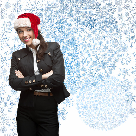 business woman in santa hat standing over blue snowflakes background photo