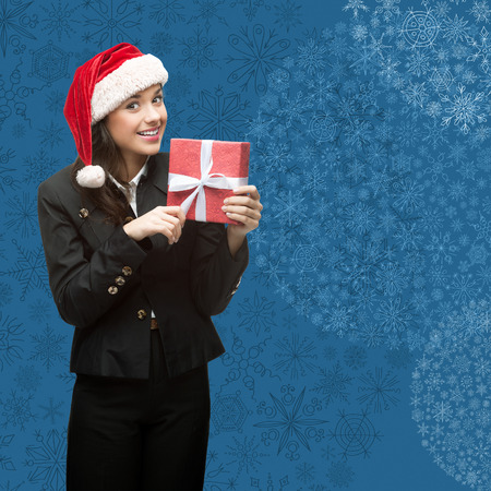 business woman in santa hat holding gift over blue snowflakes background photo