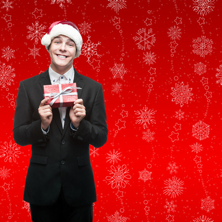 businessman in santa hat holding gift over red snowflakes background photo