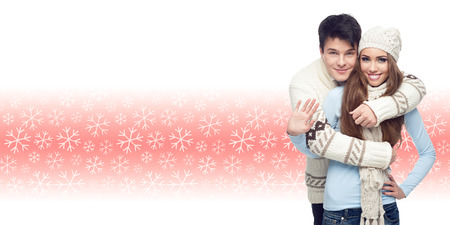 happy smiling young couple standing over winter snowflakes background photo