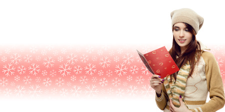 happy young woman reading christmas postcard over winter snowflakes background photo