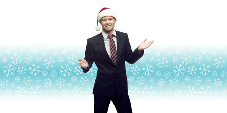 smiling young business man in santa hat showing empty space over winter snowflakes background photo