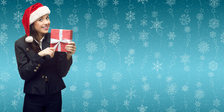 business woman in santa hat holding gift over winter snowflakes background photo