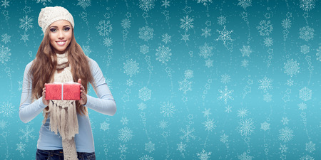 happy smiling young woman holding gift over winter snowflakes background photo