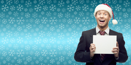 smiling young business man in santa hat holding sign over winter snowflakes background photo