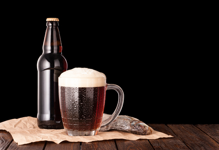 stockfish: dark cold beer in a frosty mug on dark wooden table. stockfish and brown bottle on paper