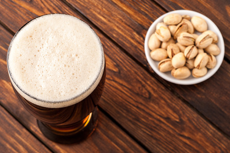 frothy: galss of dark cold frothy beer, nuts on an old wooden table