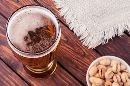 frothy: glass of light cold frothy beer, nuts, cloth on an old wooden table