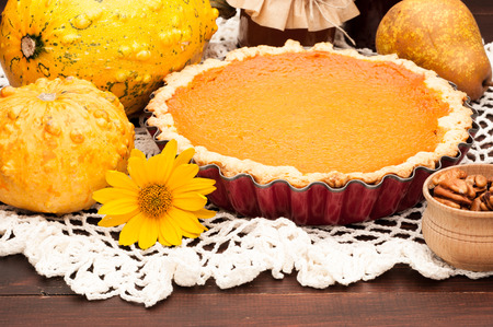 pumpkin homemade pie on wooden background arranged with food ingredients Фото со стока