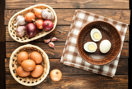 chicken eggs in basket decorated with food ingredients on an old wooden table
