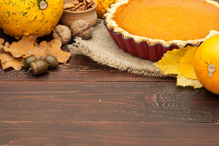 pumpkin homemade pie on wooden background arranged with food ingredients Stock Photo