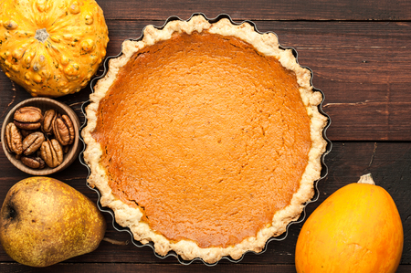pumpkin homemade pie on wooden background arranged with food ingredients top view