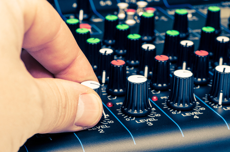 audio mixer: mans hand adjusting mixing console knobs close-up view