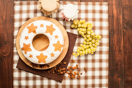 homemade traditional fruit cake on wooden stand decorated with raisins and grape top view Stock Photo