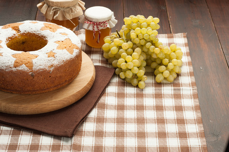 homemade traditional fruit cake on wooden stand decorated withgrape