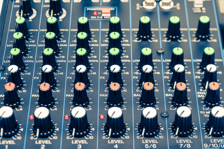 audio mixer: mixing console knobs close-up view