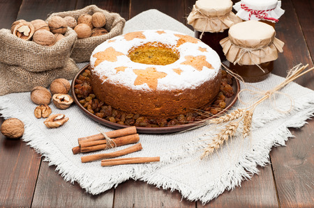 homemade traditional fruit cake on clay plate decorated with wheat ears, nuts and honey jars on wooden table
