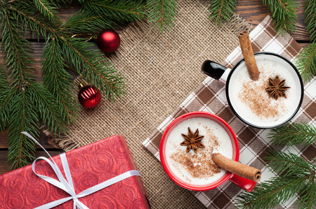 eggnog cocktail in a mug arranged with christmas decoration on wooden table