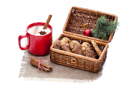 eggnog cocktail in red mug arranged with christmas decoration and cookies basket isolated on white
