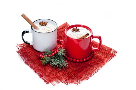 eggnog cocktail in two mugs arranged with christmas decoration isolated on white background Stock Photo