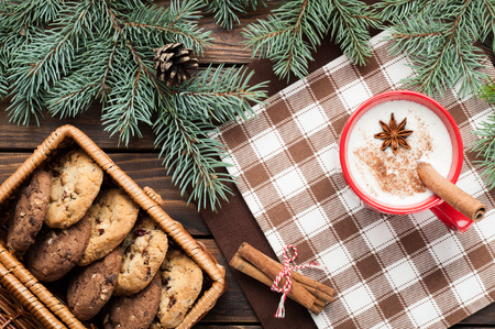 eggnog cocktail in a mug arranged with christmas decoration and cookies box on wooden table Stock Photo