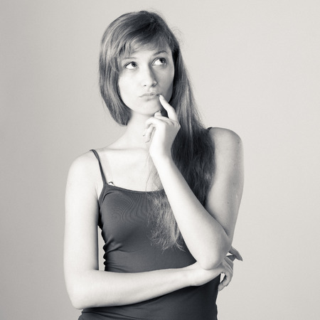 Confident beauty. Girl in casual clothes,  posing at studio on grey background.