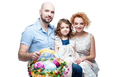Parents and daughter holding basket with Easter eggs isolated Reklamní fotografie