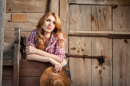 Young lady in a cowboy hat on Rustic background