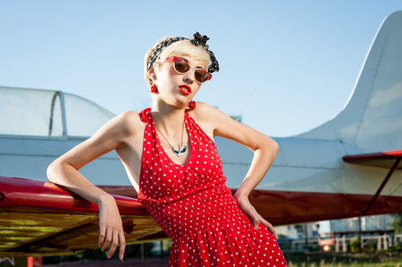 Outdoors pin-up portrait of young blond sexy caucasian woman in red retro dress 写真素材