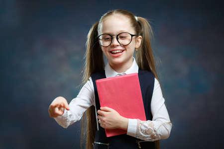 Happy Little Schoolgirl in Uniform Hold Book Tight