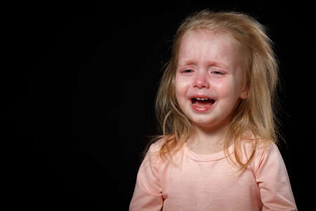 The Little Girl Is Crying Loudly, She Is Very Upset, She Is Hysterical. She Can't Calm Down. Photo In The Studio On A Dark Background Stock Photo