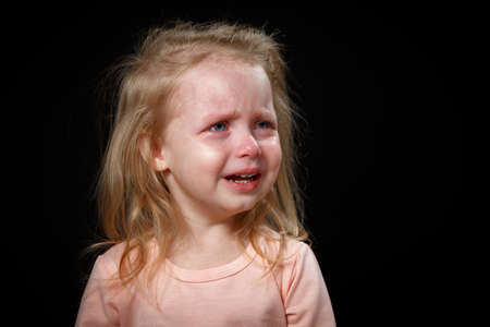 A little girl is crying hysterically in a dark room. She was badly hurt