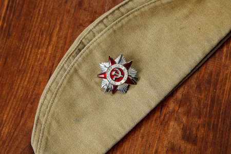 Order of the Patriotic War in St. on a Soldier's forage cap on a wooden. background