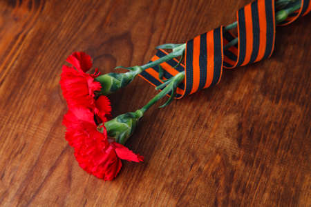 carnations and St. Georges ribbon on wooden background. selective focus image