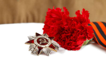 Military cap with red flowers, Saint George ribbon and orders of Great Patriotic war on white background. illustrative editorial.