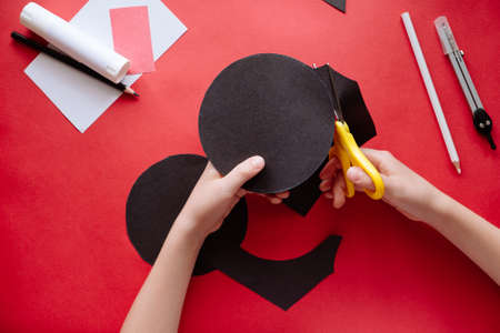 How to make bat out of paper at home. Hands making craft out of paper. Step by step photo instruction. Step 2. Cut out two circles. Children DIY art project.
