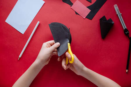 How to make bat out of paper at home. Hands making craft out of paper. Step by step photo instruction. Step 7. Cutting out the wings. Children DIY art project
