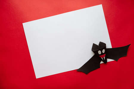 Funny Halloween Bat Made From Paper on a Red Background. Postcard on Helloween. Stock Photo
