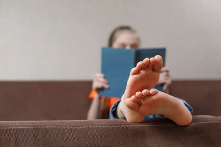 A funny little caucasian girl with feet with book while sitting on a sofa at home. Foot closeup. selective focus.