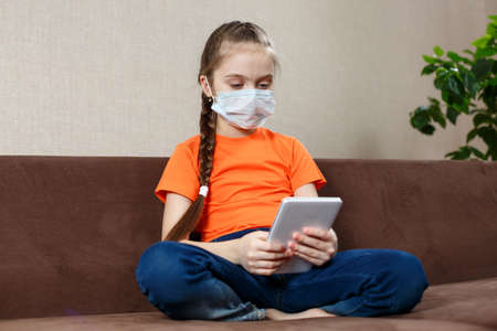 Little girl in medical mask sitting on the sofa in the Lotus position and using tablet pc. Isolation at home Standard-Bild