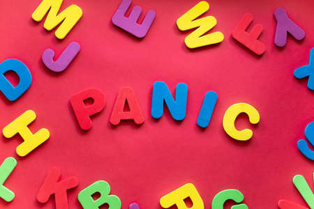 Word PANIC From Plastic Magnetic Letters On Red Background.
