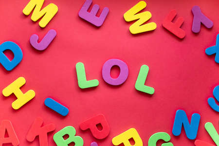 Abbreviation LOL From Plastic Magnetic Letters On Red Background.