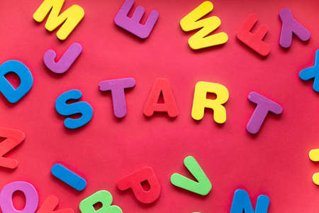 Word START From Plastic Magnetic Letters On Red Background.