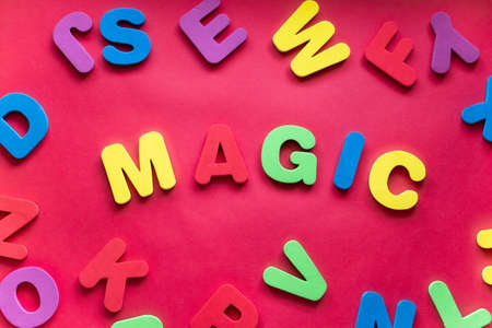 Word MAGIC From Plastic Magnetic Letters On Red Background.